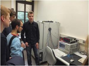 Philipp Krumm zeigt Messungen zur Temperaturabhängigkeit von Pulssignalen. Rechts im Hintergrund ein Klimaprüfschrank.